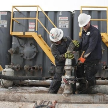 Mody Torres and Josh Anderson of Select Energy Services connect hoses between a pipeline and water tanks at a Hess site near Williston
