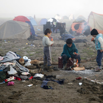 Image: Children eat by a fire at the northern Greek border station of Idomeni, Friday.