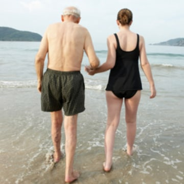 Image: Older man and young woman walking in the ocean.