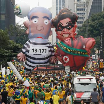 Image: Demonstrators parade large inflatable dolls depicting Brazil's former President Luiz Inacio Lula da Silva