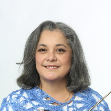 Yolanda Soto-Lopez holding knitting needles and a hook.