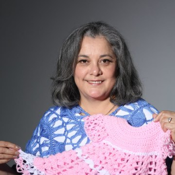 Yolanda Soto-Lopez holding a pink dress she made on her channel.