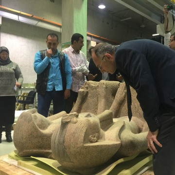 Image: Tarek Tawfiq examines the 3,500-year-old statue