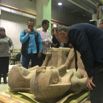 Image: Tarek Tawfiq examines the 3,500-year-old statue