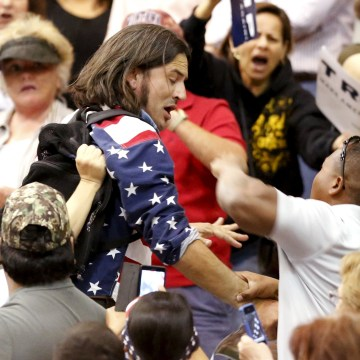 Image: A member of the audience throws a punch at a protestor as Republican Presidential candidate Donald Trump speaks during a campaign event in Tucson
