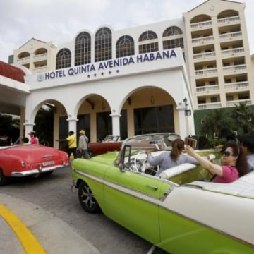 Tourists take a selfie while sitting in a vintage car outside the Quinta Avenida Habana Hotel in Havana
