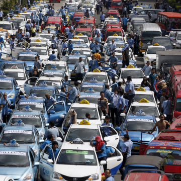 Image: Taxis taking part in a protest rally to demand the government prohibits ride-hailing apps are seen stopped on a main road in Jakarta