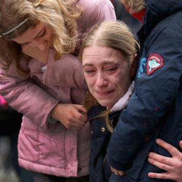 Image: A woman embraces her children at Place de la Bourse
