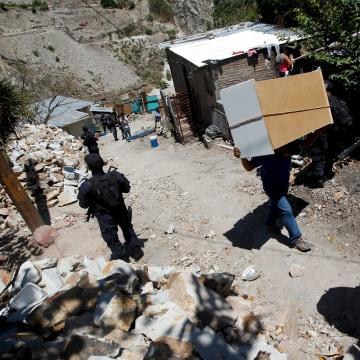 Resident carries his belongings past policemen while fleeing Las Torres neighbourhood.