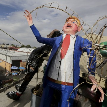Image: A craftsman works beside an effigy of U.S. Republican presidential hopeful Donald Trump at his workshop before it was burned during an Easter ritual late on Saturday in Mexico City
