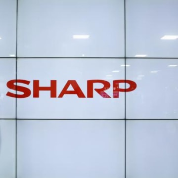 A man using his mobile phone walks past Sharp Corp's liquid crystal display monitors showing the company logo in Tokyo