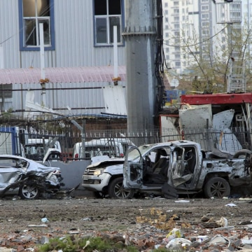 Image: A member of the police special forces stands next to vehicles, which were damaged by a car bomb attack that targeted a minibus carrying members of the police special forces, occurred in Diyarbakir
