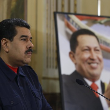 Image: Venezuela's President Nicolas Maduro speaks next to a picture of Venezuela's late President Hugo Chavez in Caracas