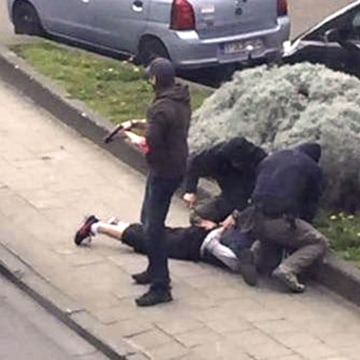 Image: Police officers detain a suspect during a raid in which fugitive Mohamed Abrini was arrested in Anderlecht in this still image taken from video