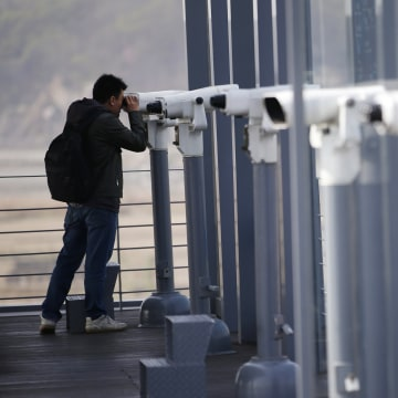 Image: A man uses binoculars to watch the North side at the Imjingak Pavilion