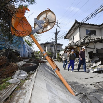 Image: Residents walk past a house damaged by a magnitude-6.5 earthquake in Mashiki, Kumamoto prefecture, southern Japan
