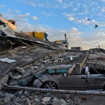 Image: A car is crashed beneath rubble in Manta, Ecuador