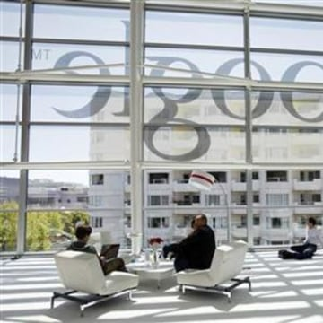 Attendees sits in front of a Google logo during Google I/O Conference at Moscone Center in San Francisco