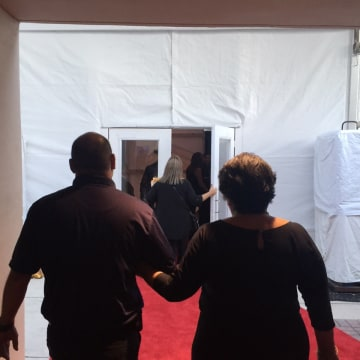 Ali Pelaez being escorted by security into the awards show.