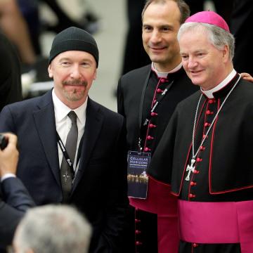 Image: U2 guitarist David Evans poses with Irish bishop Paul Tighe.