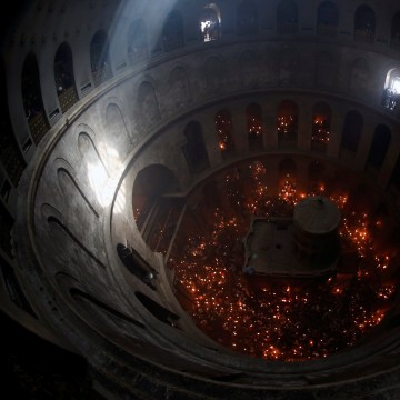 "Image: Worshippers hold candles as they part in the ""Holy Fire"" ceremony"