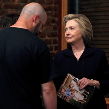 Image: U.S. Democratic presidential candidate Hillary Clinton speaks to Bo Copley about a photograph of his children during a campaign event in Williamson