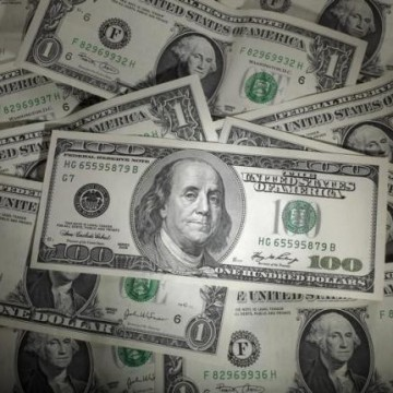 A picture illustration shows a 100 Dollar banknote laying one Dollar banknotes