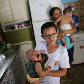 Image: Paulo, 8, holds his five-month-old sister Laura