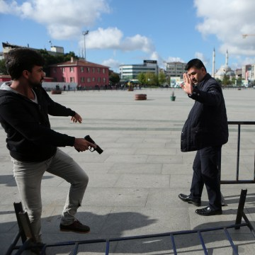 Image: Plain clothes police officers point their guns at an assailant who attempted to shoot prominent Turkish journalist Can Dundar, outside a courthouse in Istanbul