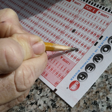 Image: A lottery player fills out numbers on a powerball form in Oakland, Calif.