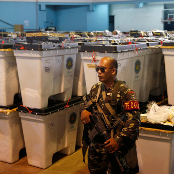Image: A soldier guards boxes containing election ballots and other paraphernalia in Davao city