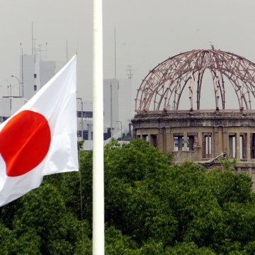 Image: The Japanese national flag flutters at half-mast in the foreground of the atomic bomb dome at the Hiroshima Peace Memorial Park, in western Japan