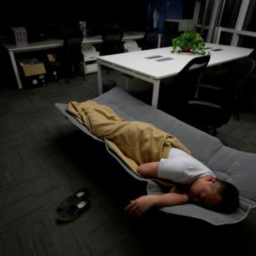 The Wider Image: Working, eating and sleeping at the office