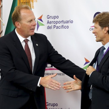 Image: San Diego Mayor Faulconer shakes hands with Mexico's Secretary of Tourism de la Madrid Cordero during the official opening of a privately funded cross border pedestrian bridge that connects the United States with Tijuana International Airport, in O