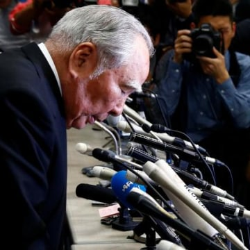 Suzuki Motor Chairman and Chief Executive Officer Osamu Suzuki bows at a news conference at the Land, Infrastructure, Transport and Tourism Ministry in Tokyo, Japan
