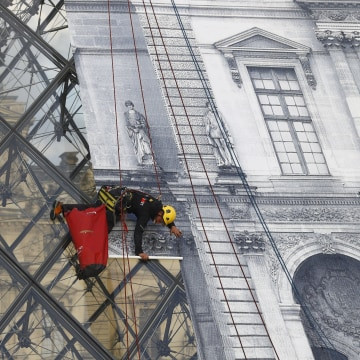 Image: Rope access technician pastes a giant picture on the Louvre Pyramid
