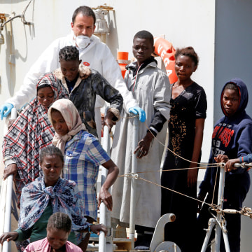 Image: Migrants disembark from the Italian Navy vessel Vega at the Reggio Calabria harbour