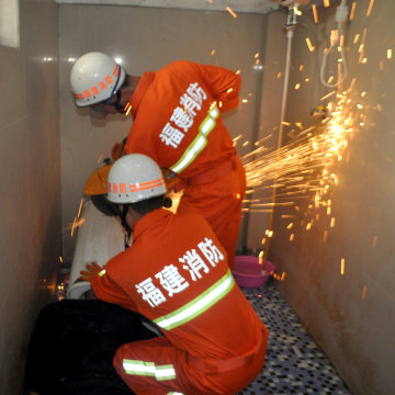 Image: Rescuers save a man with equipment as his head is stuck in a washing machine in Fuqing county of Fuzhou