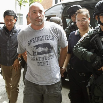 Image: Thai policemen escort an American suspect Hunter as he arrives at Don Mueang International Airport in Bangkok