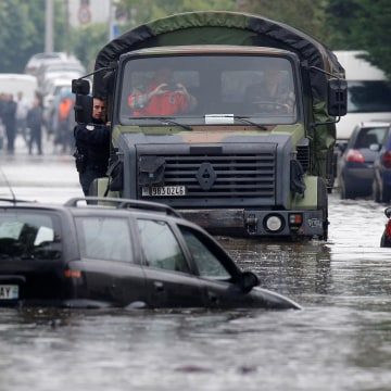Image: A police officers hangs on a military vehicle on its way through the flooded suburb of Villeneuve-Trillage in Villeneuve Saint-Georges