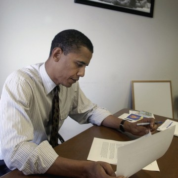 Image: Then-Democratic Senate nominee Barack Obama works near a photo of a victorious Muhammad Ali standing over his challenger