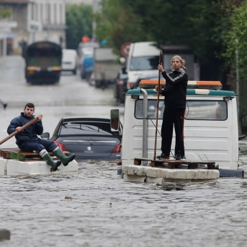 Image: Residents who refused to be evacuated sit on makeshift boats during evacuation operations of the Villeneuve-Trillage flooded suburb in Villeneuve Saint-Georges