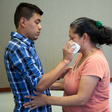 Image: Steve Hernandez wipes a tear from his mother's eye after seeing her for the first time in 20 years