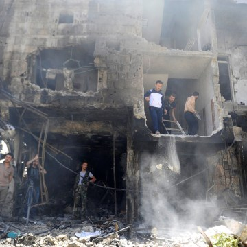 Image: People and Syrian Army members inspect a damaged site after a suicide and car bomb attack in south Damascus Shi'ite suburb of Sayeda Zeinab
