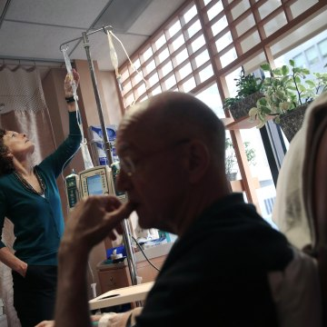 Image: Youssef Cohen, 68, undergoes cancer treatment as his wife Lindsay Wright checks his medication drip