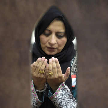 Image: Saima Qureshi prays during a special prayer with non-Muslim members