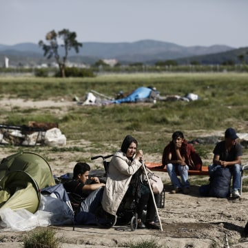 Image: Migrants wait with their belongings to leave the makeshift camp