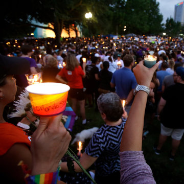 Supporters of the victims of the recent mass shooting at the Pulse nightclub hold candles while attending a vigil at Lake Eola Park, Sunday, June 19, 2016, Orlando, Fla. Tens of thousands of people attended the vigil.
