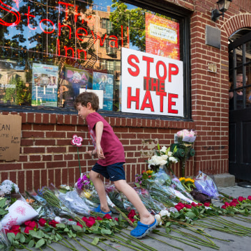 An attendee of the rally places a bouquet of flowers at a