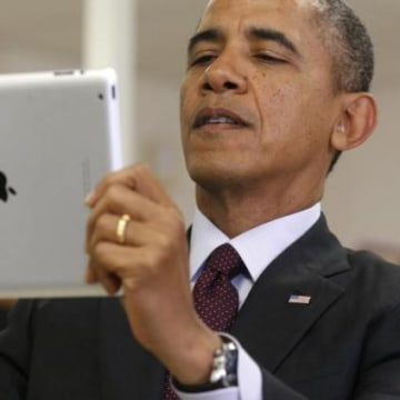 U.S. President Barack Obama holds up an iPad during a visit to Buck Lodge Middle School in Adelphi